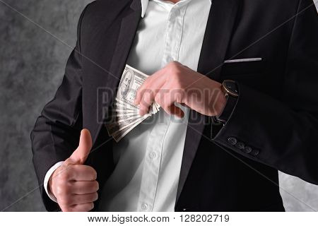 Man hiding dollar banknotes in suit on grey background