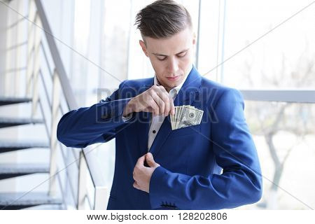 Attractive man getting dollar banknotes out of suit pocket