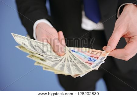 Man in a suit holding fan of dollar and euro banknotes on blue background