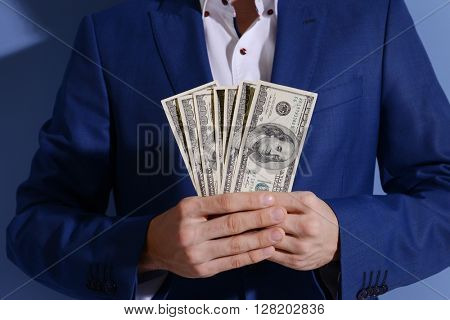 Man in a suit holding fan of dollar banknotes on blue background