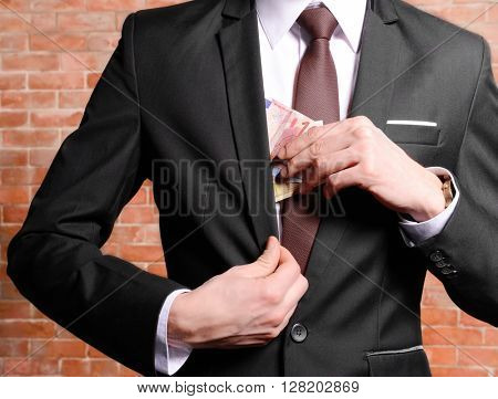 Man hiding euro banknotes in suit on brick wall background