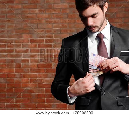 Attractive man hiding euro banknotes in suit on brick wall background