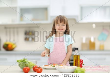 Little girl with a plate of vegetable salad.