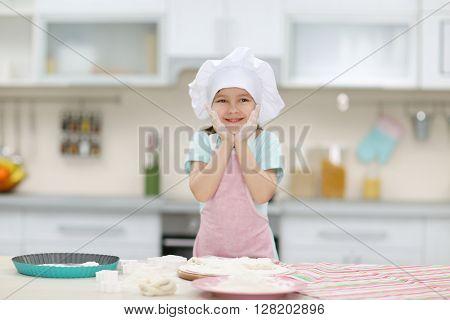 Beautiful little girl making the dough.