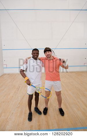 Squash players posing on squash court for photographer. Two men are going to have competition in squash.