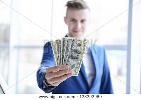 Attractive man in a suit holding a fan of dollar banknotes against the window