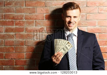 Attractive man in a suit holding fan of dollar banknotes on brick wall background
