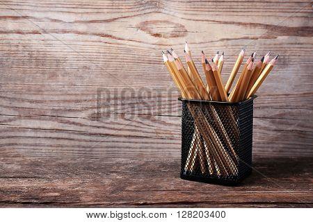 Set of pencils in metal holder on wooden background