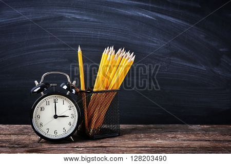 Set of pencils in metal holder and alarm clock on blackboard background