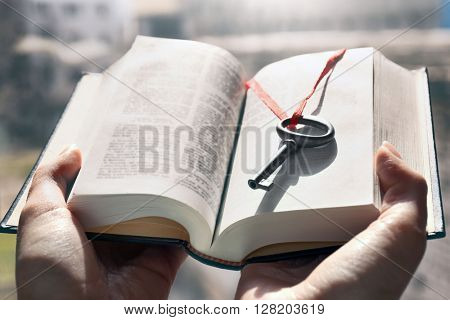 Hands holding a book with vintage key in it. Close up