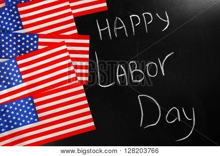 Happy Labour Day text and USA national flags on blackboard