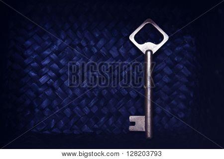 Old key on blue wicker background