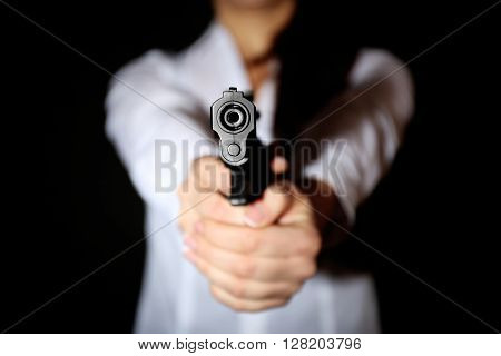 Woman holding handgun on dark background