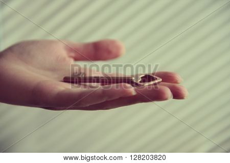 Female hand holding old key closeup