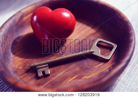 Old key with red heart on wooden background