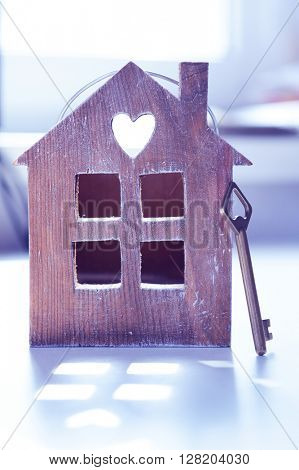 Old key with small wooden house closeup