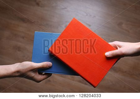 Male and female hands holding books on wooden background.