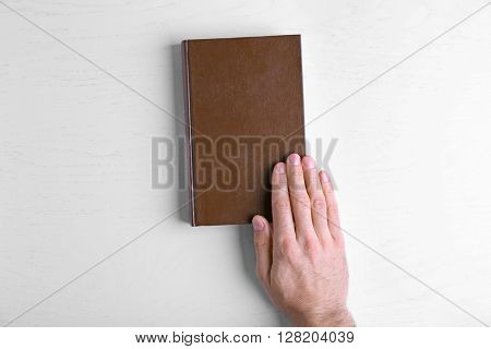 Male hand hold the brown book on white table.