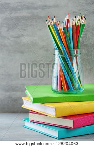 Books and pencils in glass jar on grey background