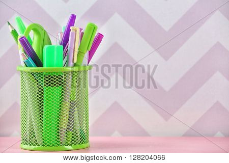 Pens, pencils and markers in metal holder on colour background