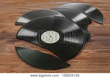 Broken old vinyl records on wooden background