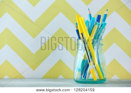 Stationery in glass jar in front of wall background