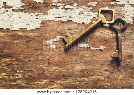 Two keys on old crack wooden background