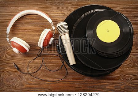 Stack of old vinyl records with headphones and microphone on wooden background