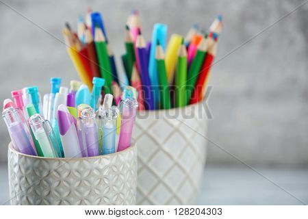 Pens and pencils in cups in front of wall background