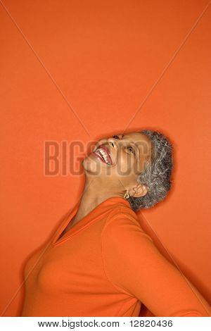 African American mature adult female with head back smiling.