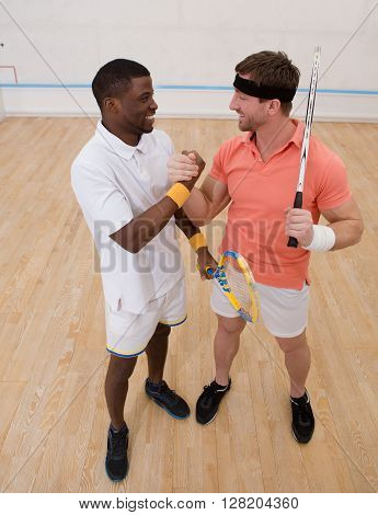 Two men playing match of squash. Handsome men having competition on squash court. Happy smiling and shaking hands.