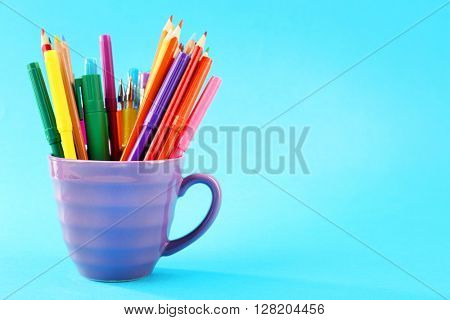 Colorful stationery in cup on blue background