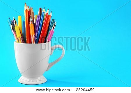 Colorful stationery in white cup on blue background