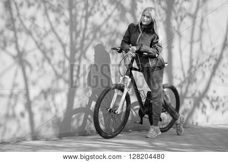 Young blonde girl is standing near bike