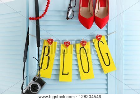 The word BLOG from cutout paper pieces with female shoes, glasses and retro camera on blue board background