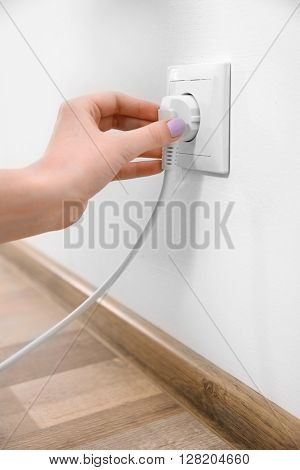 Woman with power outlet and plug