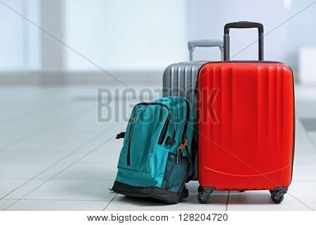 Different suitcases on tile floor