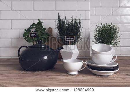 Trio of Herbs Growing Variety of Containers on Modern Wooden Kitchen Counter with Tea Pot, Cups and Saucers in Foreground. 3d Rendering.