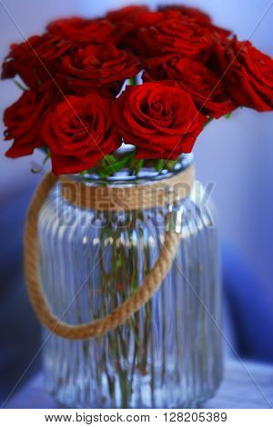 Red roses in a glass jar in the room