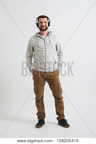 A young happy man in casual clothes with headphones on his head is listening music