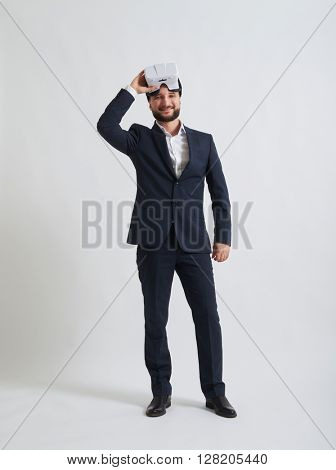 Businessman in a formal wear likes the 3d effect made by virtual reality glasses