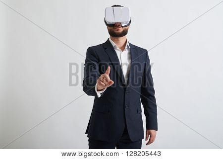 Close up of businessman in a formal wear and virtual reality glasses who trying to touch something with his hand
