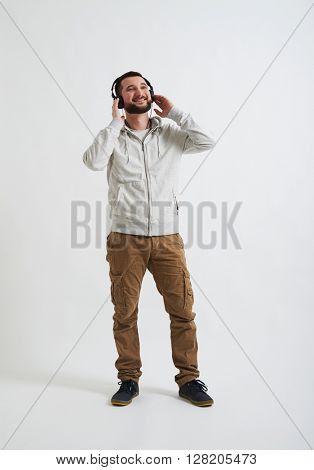 A young Caucasian bearded man in casual wear is smiling and listening to music with his headphones on