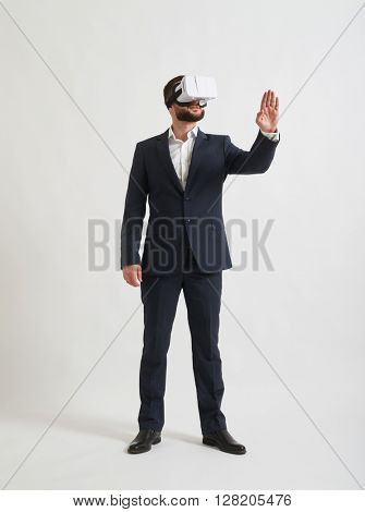 A young Caucasian businessman is watching something in virtual reality glasses and trying to touch something with his hand