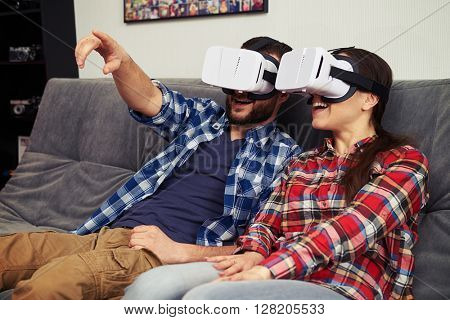 A young man and woman in casual clothes and virtual reality glasses is watching something and man showing something in front of him