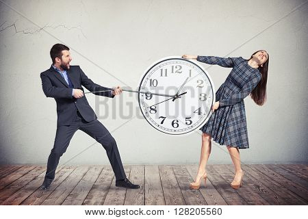 A young woman in checkered dress is intensively holding the big round clock while the man in dark business suit is pulling an hour-hand as if trying to slow down the time