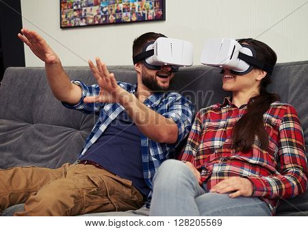 A young man and woman in casual clothes having fun using white virtual reality glasses