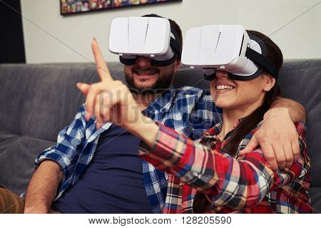 A young man and woman in casual clothes and virtual reality glasses is watching something and woman trying to touch something in front of her