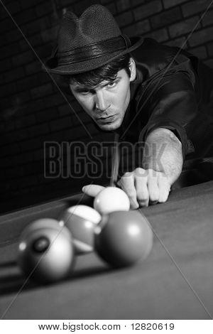 Prime adult Caucasian retro male shooting pool.