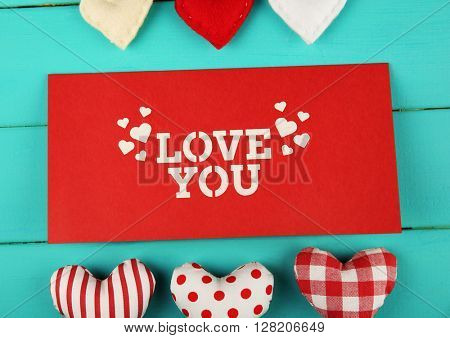 Valentine's Day concept. Composition of colourful handmade hearts and gift cards on turquoise wooden background